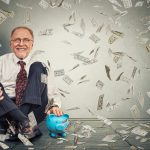 Excited happy senior man sitting on a floor with piggy bank under a money rain