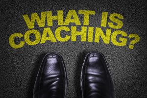 Top View of Business Shoes on the floor with the text: What Is Coaching?